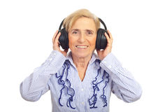 Happy senior woman listening in headphones Royalty Free Stock Photo