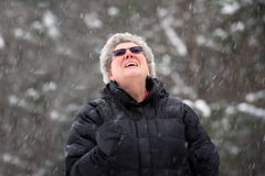 Happy Senior Woman Looking Up on a Snowy Day Royalty Free Stock Image