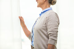 Happy senior woman looking through window at home Royalty Free Stock Photos