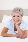 Happy senior woman lying in bed Stock Photo