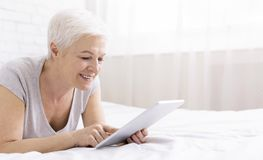 Happy senior woman lying in bed and using digital tablet stock photos