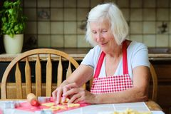 Happy senior woman making cookies at the kitchen Stock Photo