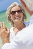 Happy Senior Woman Man Couple On Tropical Beach. Happy senior women with perfect teeth dancing with men in a couple and holding hands on a deserted tropical Stock Images