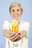 Happy senior woman offer a glass with orange juice Royalty Free Stock Photo