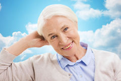 Happy senior woman over blue sky and clouds Stock Photos