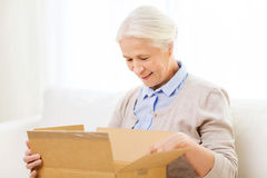 Happy senior woman with parcel box at home Royalty Free Stock Photos