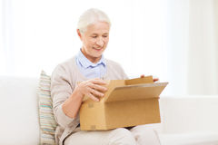 Happy senior woman with parcel box at home. Age, delivery, mail, shipping and people concept - happy smiling senior woman looking into open parcel box at home Royalty Free Stock Photos