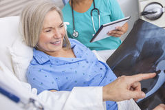 Happy Senior Woman Patient in Hospital Bed. Happy senior women patient recovering in hospital bed with male doctor and female nurse looking at hip replacement x Stock Photo