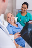 Happy Senior Woman Patient in Hospital Bed. Happy senior women patient recovering in hospital bed with male doctor and female nurse looking at hip replacement x royalty free stock photos