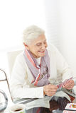 Happy senior woman playing cards Royalty Free Stock Photo