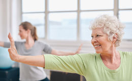 Happy senior woman practicing yoga at gym class. Royalty Free Stock Photo