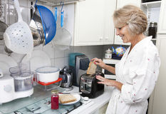 Happy senior woman preparing toast in domestic kitchen Stock Photos