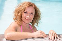 Happy senior woman in private home pool summer. Portrait happy senior woman in private home pool summer Royalty Free Stock Images