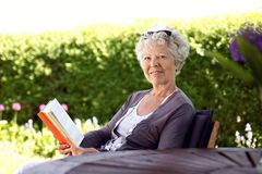 Happy senior woman reading book in the garden. Happy senior woman with book in hand sitting in her backyard looking at camera smiling - Elder woman reading novel Stock Photography