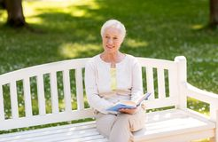 Happy senior woman reading book at summer park. Old age, retirement and people concept - happy senior woman reading book sitting on bench at summer park Stock Images