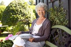 Happy senior woman reading newspaper in backyard stock photo