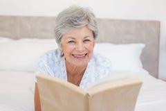 Happy senior woman reading story book Royalty Free Stock Photo