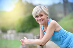 Happy senior woman relaxing after jogging stock photography