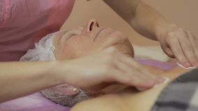 Beautician makes facial cleansing and exfoliating stock footage