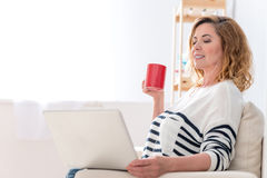 Happy senior woman resting with computer at home Royalty Free Stock Photo