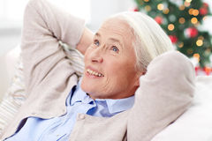 Happy senior woman resting on sofa at home Stock Images