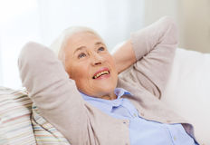 Happy senior woman resting on sofa at home Royalty Free Stock Photography