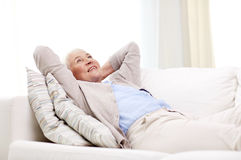 Happy senior woman resting on sofa at home Royalty Free Stock Photo