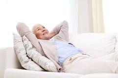Happy senior woman resting on sofa at home Royalty Free Stock Photo