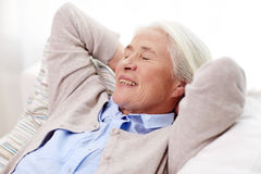 Happy senior woman resting on sofa at home Stock Photography