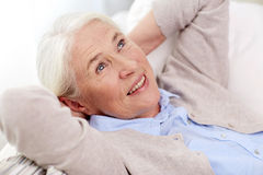 Happy senior woman resting on sofa at home Stock Photos