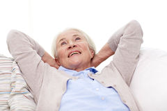 Happy senior woman resting on sofa at home Royalty Free Stock Photos