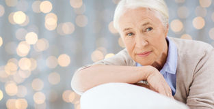 Happy senior woman resting on sofa over lights Royalty Free Stock Photo