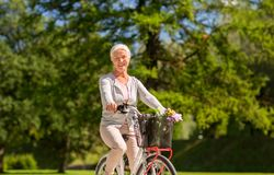 Happy senior woman riding bicycle at summer park. Active old age, people and lifestyle concept - happy senior woman riding fixie bicycle at summer park royalty free stock images