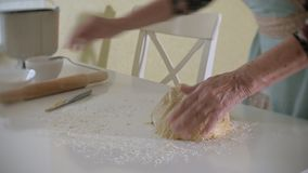 Happy senior woman rolling pizza dough at home in the kitchen stock footage