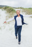 Happy senior woman running at beach Royalty Free Stock Photography