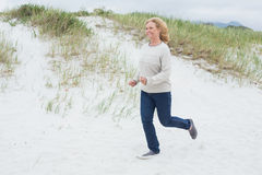 Happy senior woman running at beach Stock Image