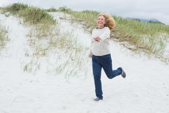 Happy senior woman running at beach Stock Photography