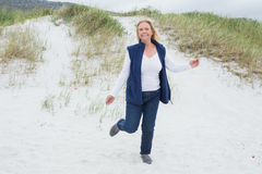 Happy senior woman running at beach Stock Photos