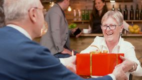 Happy senior woman when she`s receiving a red gift box from her husband during their date. Happy senior women when she`s receiving a red gift box from her royalty free stock image