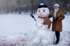 Happy senior woman sculpt and hug a big real snowman. In winter park Royalty Free Stock Image