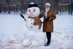 Happy senior woman sculpt a big snowman in winter. Happy senior woman sculpt and hug a big real snowman in winter park Stock Image