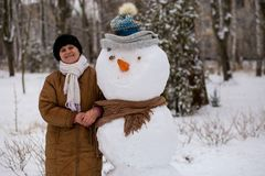 Happy senior woman sculpt and hug a big real snowman. In winter park Stock Image