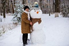 Happy senior woman sculpt and hug a big real snowman in winter. Park Stock Image