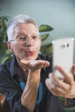 Happy senior woman sending kiss over skype Stock Images