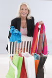 Happy senior woman with shopping bags iat home checking purchasi Royalty Free Stock Photos