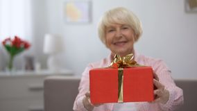 Happy senior woman showing gift box at camera, birthday celebration, present. Stock footage stock video