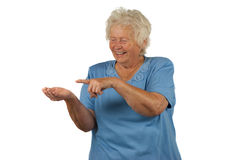 Happy senior woman is showing and looking at your Stock Images