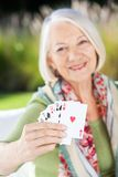 Happy Senior Woman Showing Playing Cards Royalty Free Stock Photography