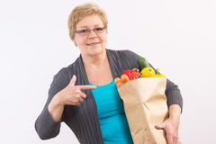 Happy senior woman showing shopping bag with fruits and vegetables, healthy nutrition in old age stock images