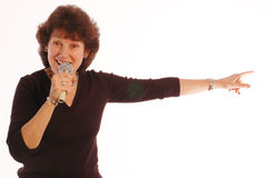 Happy senior woman singing Microphone in hand  Royalty Free Stock Images